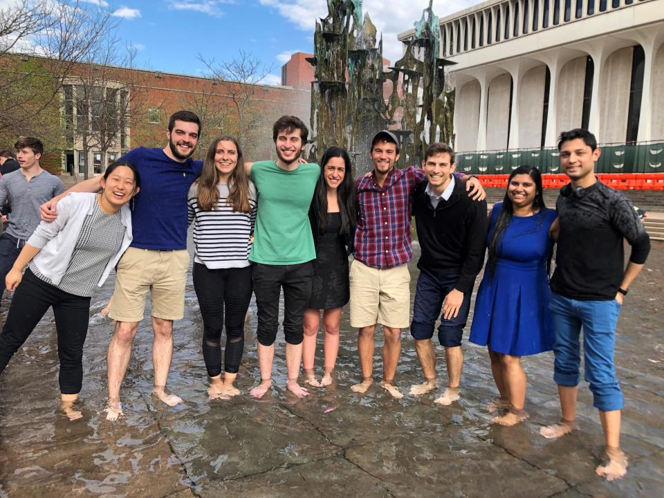 9 ORFE students standing in fountain on senior thesis turn in day.