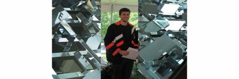Benjamin Laufer with award in hand.  Silver geometric designs on either side of his picture.